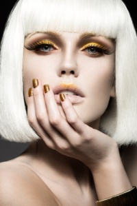 Beautiful girl in a white wig, with gold makeup and nails. Celebratory image. Beauty face